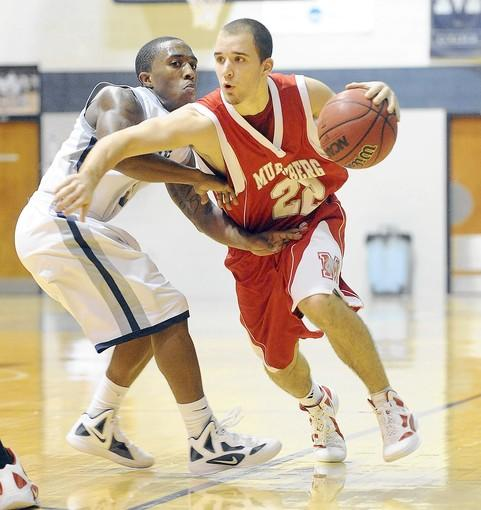 Muhlenberg's Austin Curry (22) right, drives past Moravian's D.J. Strayhorn (3) left, in the first half at Johnston Hall in Bethlehem November 15, 2011.