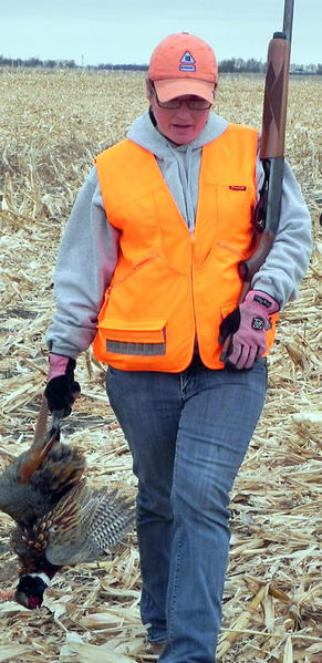 Kim Eddy of Woonsocket walks out of the field with her rooster she shot at the Sixth annual Womens Pheasant Hunt near Cavour. The hunt was sponsored by Hurons Heartland Region Pheasants Forever chapter.