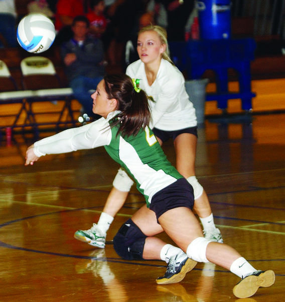 Roncalli's Brittany Holzer (2) digs the ball as teammate Taylor Hanson looks on.