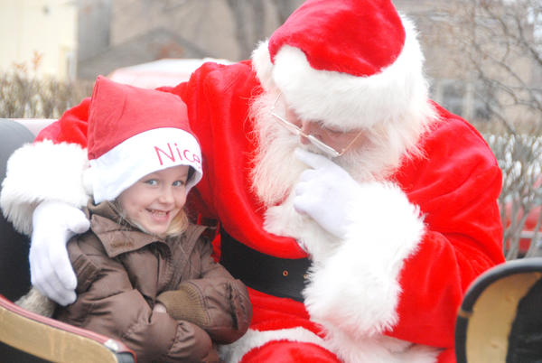 Santa Claus whispers to a little elf during last year's Stafford's Downtown Petoskey Holiday Parade.