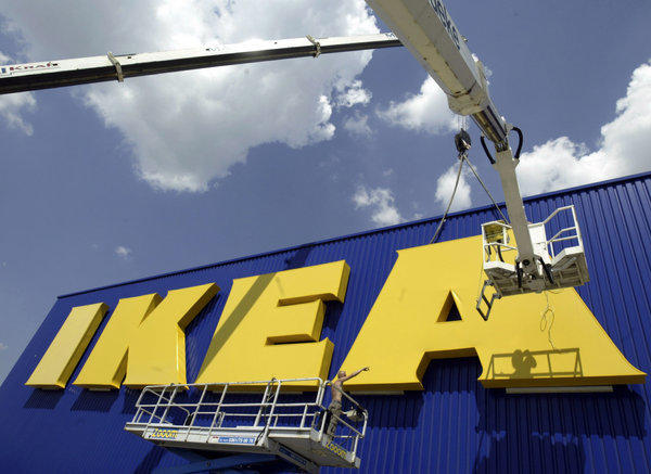 Workers affix the Ikea logo to a new store in eastern Germany. Ikea published a report showing that the company benefited from forced labor in communist East Germany.