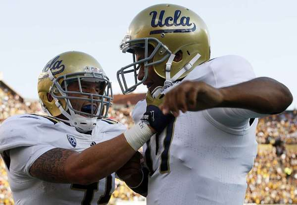 UCLA quarterback Brett Hundley is congratulated by fullback David Allen after a touchdown run against Colorado.