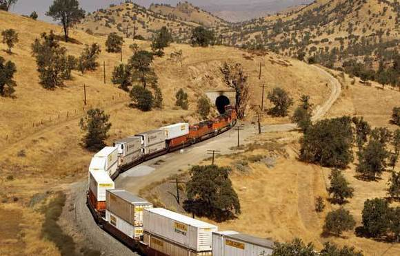 A freight train slowly descends in the Tehachapi Mountains, near the route California's bullet train will eventually take. A year has been added to construction of the first leg of the high-speed rail system.