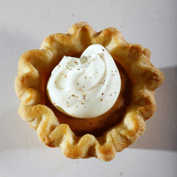 A pumpkin chiffon mini-pie is topped with whipped cream and nutmeg.
