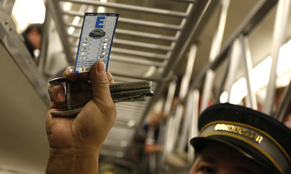 Metra conductor Joseph Velazquez punches a 10-ride ticket on a northbound Metra train in 2010.