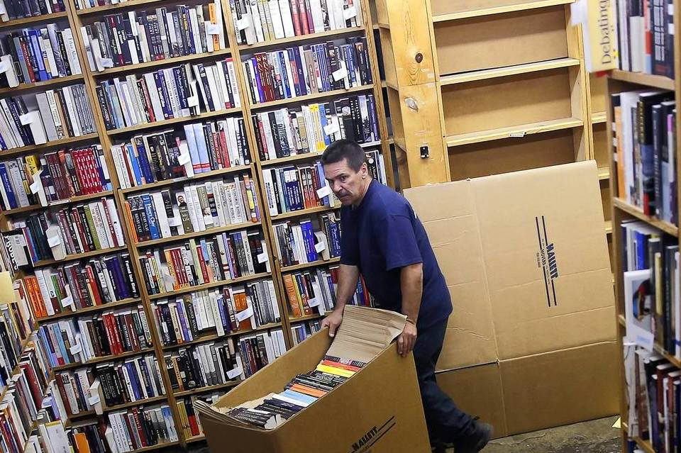 Robert Mack, a mover with Hallett Movers, moves boxes of packed books for a move at Seminary Co-Op Bookstore located at 5757 S. University Ave. After 50 years in its current location in the basement of the Chicago Theological Seminary, the bookstore is moving to 5751 S. Woodlawn Ave., a few blocks away.