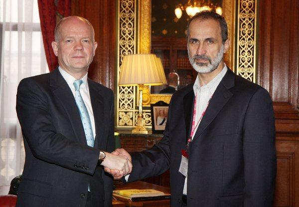 British Foreign Secretary William Hague, left, greets President Mouaz Khatib of the Syrian National Coalition for Opposition and Revolutionary Forces in London.