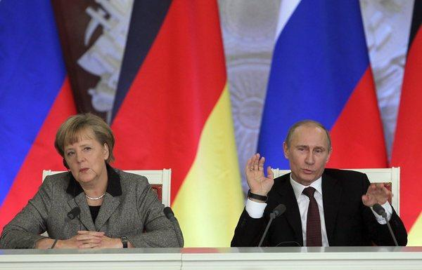 German Chancellor Angela Merkel, left, and Russian President Vladimir Putin speak at a news conference after the 14th German-Russian inter-governmental consultations at the Kremlin in Moscow.