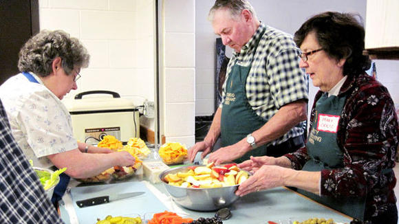 Behind the scenes of a previous Thanksgiving Community Dinner, Carol Duhoski, Joe Duhoski and Mary Cruz prepare cheese, fruit and relish trays for the predinner appetizer table
