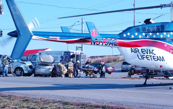 Emergency medical personnel prepare to load the driver of the gold Mazda, seen at left from rear, into an awaiting helicopter following a two-car collision on the Danville bypass Friday afternoon.