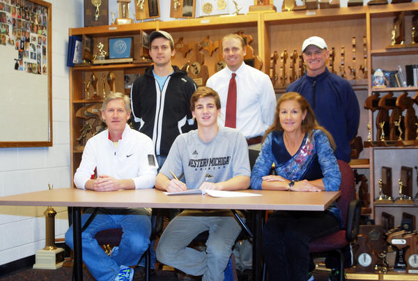 Petoskey senior Zach Phillips (front, center) signs a national letter of intent to play tennis at Western Michigan University Thursday at the Petoskey High School athletic office. Joining Phillips at his signing is (front, from left) father Brian Phillips, mother Jana Phillips; back, coach Collin Price; Petoskey High School boys tennis coach John Boyer and coach Doug Dickenson.