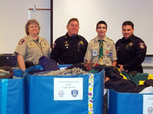 From left, Corrections Ltd. Lynne Woodruff, Sheriff Pat Perez, Ted Spiro and Undersheriff David Wagner with Spiro's donation of coats.