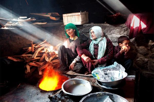 Raza Gul, center, sits with her son and her sister-in-law in the Kabul bakery where they eke out a living.