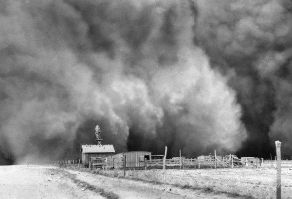 "About to be engulfed in a gigantic dust cloud is a peaceful little ranch in Boise City, Oklahoma where the top soil is being dried and blown away. This photo was taken on April 15, 1935 and is included in Ken Burns' PBS documentary ""The Dust Bowl."""