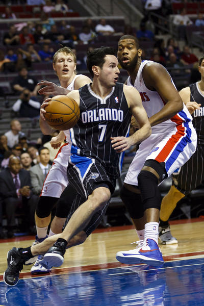 Orlando Magic shooting guard J.J. Redick (7) drives against Detroit Pistons center Greg Monroe (10) and small forward Kyle Singler (25) in the first quarter at The Palace.