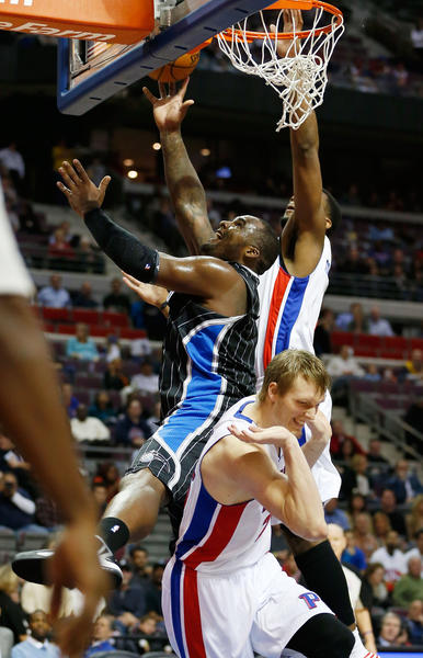 Glen Davis #11 of the Orlando Magic gets a shot off between Kyle Singler #25 and Greg Monroe #10 of the Detroit Pistons at the Palace of Auburn Hills on November 16, 2012 in Auburn Hills, Michigan.