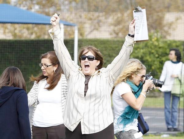 Mariners Christian school administrator Sheri McDonald cheers when she learns one of the golf balls that were dropped from a helicopter onto the athletic field landed in one of the holes, winning her a hot chocolate.