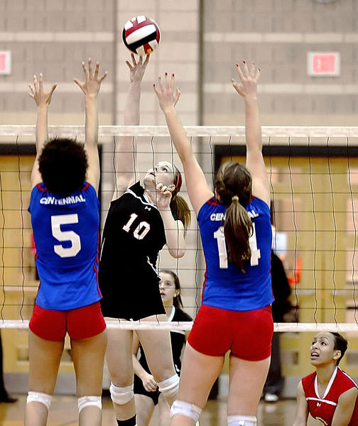 North Hagerstown's Peyton Wallech tips over the reach of Centennial's Jessie Link (5) and Kristen Ritchie in the third set of the Hubs' sweep in the Maryland Class 3A volleyball final at the University of Maryland on Friday.