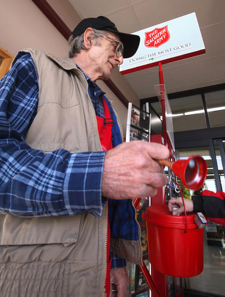 Frank Cascio of Aberdeen, a volunteer bell ringer for the Salvation Army, watches as someone puts a donation in the red kettle Friday at Ken's SuperFair Foods. The annual bell-ringing campaign began for the season Friday.