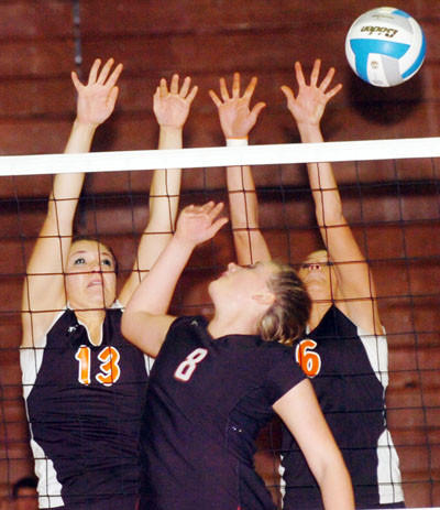 Mobridge-Pollock¿s Ariel Bieber (13) and Kady Pinney (6) try to block a shot by Jessa Doom of Wagner at the State A volleyball tourney in Watertown Friday. 5Watertown Public Opinion Photo by Roger Merriam