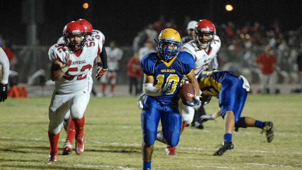 Issak Camparan of Brawley Union High makes his way to the goal line in the third quarter with Imperial defense closing in Friday evening in Brawley.