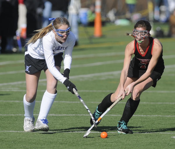 Darien's Kelsey Bumgardner, 10, left, battles Cheshire's Danielle Bellantonio, 7,  during the second half. The state high school field hockey championships took place Saturday at Cottone Field at Wethersfied High School in Wethersfield.