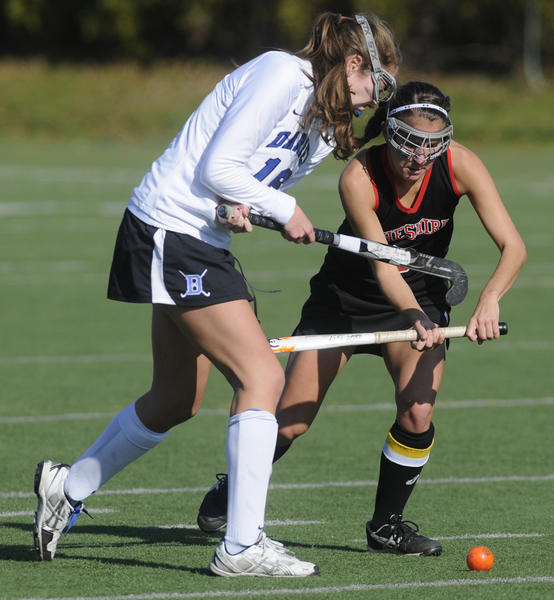 Darien's Maggie Wells, 16, battles  Cheshire's Miranda Garcia, 5, during the second half. The state high school field hockey championships took place Saturday at Cottone Field at Wethersfied High School in Wethersfield.