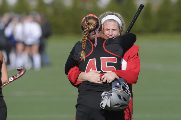 Cheshire's goalie, Lauren Fountain, 00, is consoled by teammate Emma Farrel, 45, after their loss. The state high school field hockey championships took place Saturday at Cottone Field at Wethersfied High School in Wethersfield. Darien beat Cheshire by a score of 4 to 0 to win the  Class L championship.