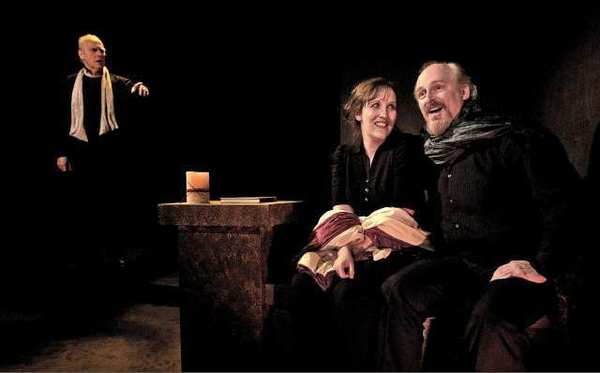 "David Allen Jones as ""Scrooge,"" and Kate Danley and Frank Simons as the ""Cratchits,"" in the Grove Theater Center production of a ""A Christmas Carol."""