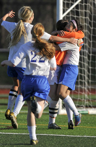 Youn Jae Baek, far right, celebrates with Avon teammate Kaylan Conrad after victory over Pomperaug in the class L girls soccer semifinal at West Haven High School Saturday.