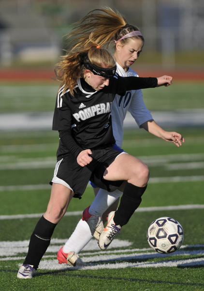 Pomperaug's Trachel Meier, left, battles Avon's Hunter McCarthy, during a class L girls soccer semifinal at West Haven High School Saturday.