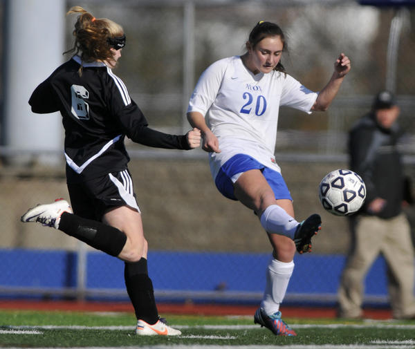 Avon's Michaela Marcus gets a shot off as Pomperaug's Rachel Meier defends during the Class L girls soccer semifinal at West Haven High School Saturday.
