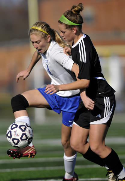 Avon's Hannah Davey shields Pomperaug's Chloe Benoit during the Class L girls soccer semifinal at West Haven High School Saturday.