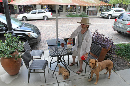 Ray Forthuber, 54, pours water for his two dogs, Abbey, left, and Jeb, in front of the Panera Bread along Park Ave. in Winter Park, Fla. where they reside most days.  Ray and his wife are homeless, living out of their car along the streets of Winter Park near Park Ave.  Friday, September 28, 2012.