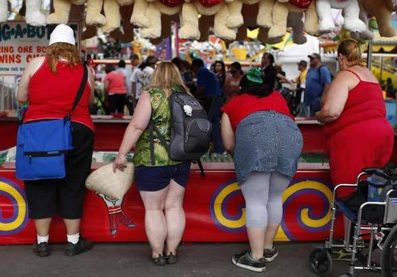 Fairgoers play a carnival game at the San Diego County Fair in Del Mar, Calif.