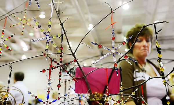 Beaded Star Flakes made by Angie Jacobs of Urbana, Md., are looked over by Sharon Bitner of Chambersburg, Pa., at the annual Kris Kringle Craft Show on Saturday.
