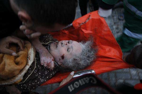 Palestinian paramedics carry an injured woman after an Israeli air raid in Beit Lahiya, northern Gaza Strip.