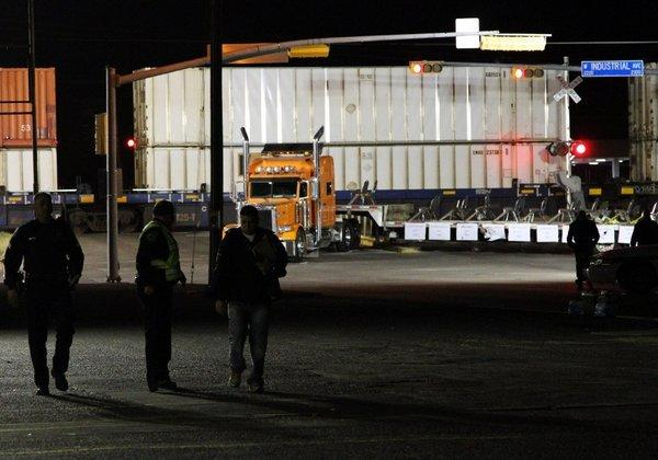Police officers walk in front of a trailer that was carrying wounded veterans in a parade when it was struck Thursday by a train in Midland, Texas.