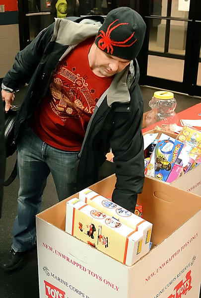Brent Roberts of Clear Spring places a toy in a box before a hockey game at Hagerstown Ice & Sports Complex Saturday evening.