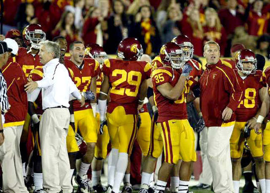 USC Coach Pete Carroll and an assistant try to keep the Trojans on their sideline after some words were exchanged with the Bruins and players spilled onto the field in the final minute of the game Saturday night.