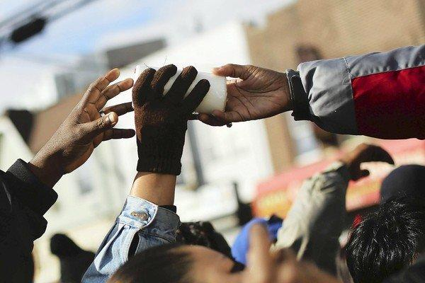 Residents of New York's Rockaway Peninsula reach for candles being handed out by a group called Dream Center two weeks after Superstorm Sandy hit.