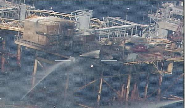 In this handout image provided by the U.S. Coast Guard, commercial vessels spray water to extinguish a platform fire onboard West Delta 32.