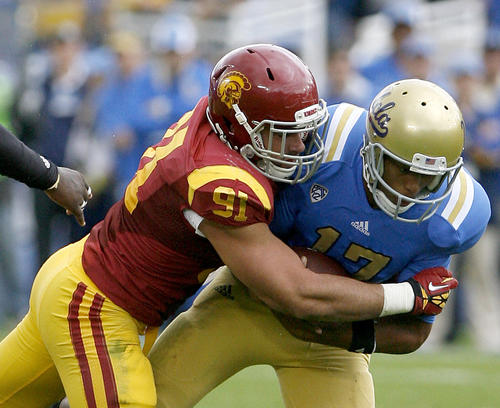 UCLA's QB #17 Brett Hundley is tackled by USC's #91 Morgan Breslin during game vs. USC at the Rose Bowl in Pasadena on Saturday, November 17, 2012.
