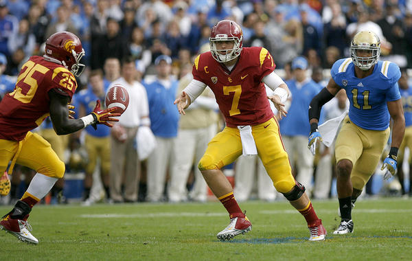 UCLA's #11 Anthony Barr looks to make a tackle as USC QB Matt Barkley pitches the ball to #25 Silas Redd during game vs. UCLA at the Rose Bowl in Pasadena on Saturday, November 17, 2012.