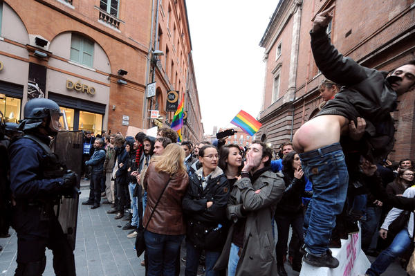 A man shows his buttocks to police as people take part in a demonstration in support of same-sex marriage on November 17, 2012 in Toulouse, southern France.