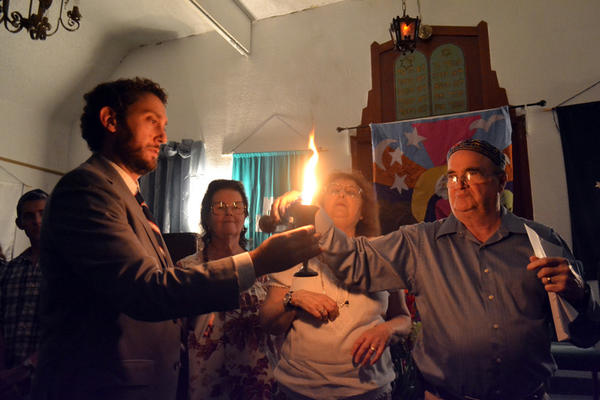 Wayne Harvie (left) puts a braided candle into a cup of juice that Student Rabbi Zachary Zysman holds during the Havdalah at the Interfaith Thanksgiving service at Temple Beth Jacob in El Centro on Saturday.