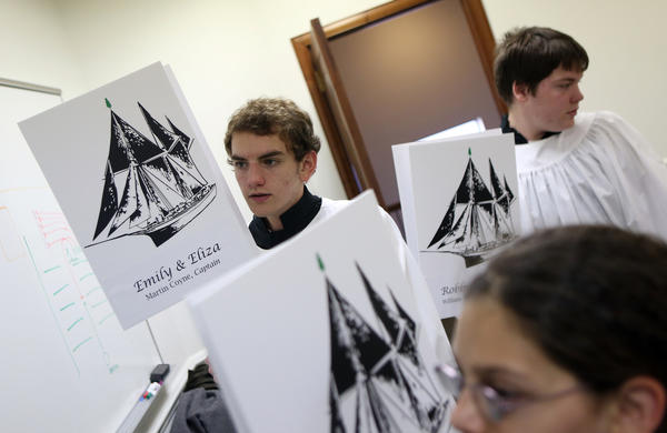 Christian Mergl (left), 15,  looks over his instructions before taking part in a procession of Christmas tree ships during a celebration of Christmas tree ship Captain Herman Schuenemann, on the 100th anniversary of the sinking of the Rouse Simmons off the coast of Wisconsin. The procession was part of a service at  St. Pauls United Church of Christ in Chicago.