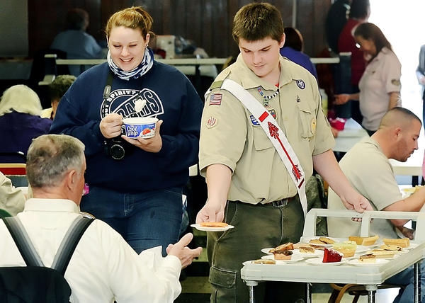 Meghan McDougall, left, and Boy Scout Dillon Hutson serve pie and whipped topping Sunday at a Thanksgiving dinner at the Moose Lodge in Williamsport.
