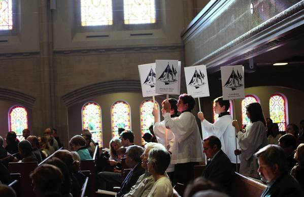 Acolytes enter the service with banners acknowledging the Christmas tree ship's captain for the 100th anniversary of the sinking of the Rouse Simmons off Wisconsin. The procession was part of a Sunday service at St. Pauls United Church of Christ in Chicago.