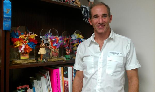 Guy Berkebile stands with his Ironman World Championship trophies in his office at Guy Chemical.